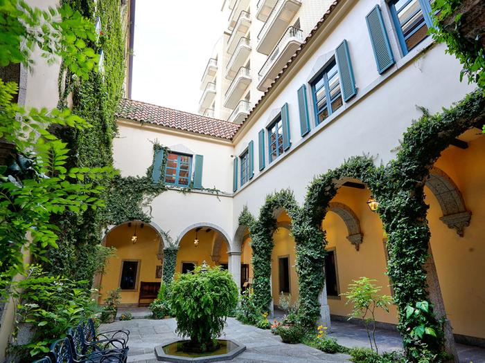 アーチ型が特徴的な廊下の横には緑豊かな中庭が広がり、中央には噴水が。館内に入ると一気に異国情緒漂う空間に。間隔をあけて吊るされた灯りがよりムードを高めています。