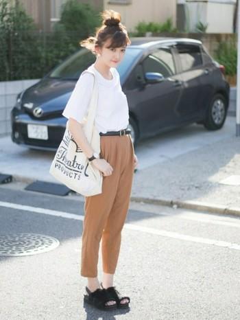 白Tシャツとベージュのテーパードパンツのシンプルコーデにに、黒のロゴやベルトと靴を合わせて程よく引き締めています。