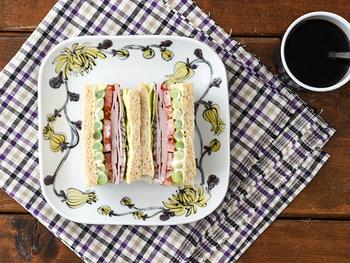 贅沢にたっぷりの具材をはさんだサンドイッチ。鮮やかな切り口を盛り立てるように、お皿に書かれたお花が取り囲みます。これだけで栄養がたっぷりとれる、元気が出そうな朝ごはんです。クロスを無造作に敷くだけでも、テーブルが華やぎますね。