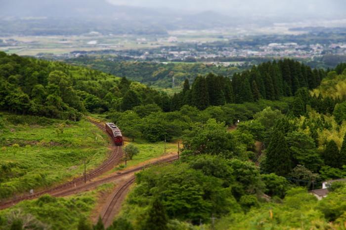 大畑駅は、秘境駅として有名であるほか、日本で唯一のスイッチバックとループ線を併せ持つ駅でもあります。周辺の高台から眺める大畑駅の眺望は格別です。遠くに見える大畑集落、駅を取り囲む緑の森、環状とジグザグの線路、小さな赤い列車が織りなし、絵画のような景色が広がっています。