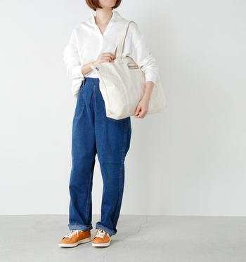 ワッペンがアクセントになった「THE NORTH FACE(ノースフェイス)」のビッグキャンバスバッグ。ワッペンの刺繍のオレンジとスニーカーのカラーをリンクさせた、ヴィンテージライクなデニムスタイルです。