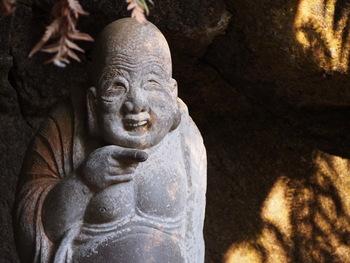 浄智寺・裏山のやぐら内にいるのが、愛嬌のある「布袋尊」。指差す方向に福あり、お腹を撫でると元気がもらえるのだとか。