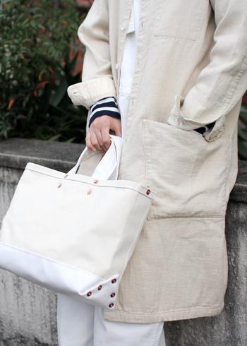 こちらのトートは、職人の道具入れとして使われていたアメリカの古いトートバッグをお手本に作られています。持ち手と底布が、防水性のあるエステル帆布。内部には使いやすいポケットやキーフックなど気配りの機能がいろいろ。