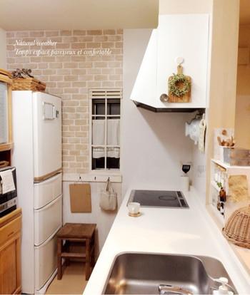 キッチン横の壁にレンガ風のリメイクシートを貼って。白を基調としたナチュラルなキッチンにマッチしています。