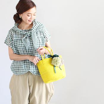 ざっくりと編まれたかごバッグには丸いフォルムのお花を添えて。初心者でもバッグなら差し色イエローとしてチャレンジしやすいですね。