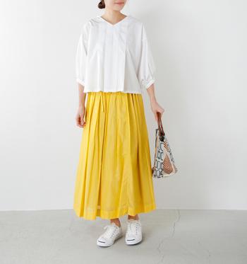 たっぷりとギャザーをとったコットンスカートは、透け感があって軽やかに見えます。エアリーなイエローはやさしい印象ですね。