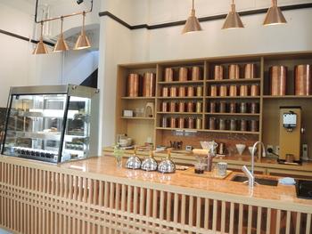 カウンターの向こうに整然と納まる大小さまざまな銅の茶筒たち。店の壁にあるランプシェードは、すべて、日々、茶筒と向き合う職人が手掛けたもの。