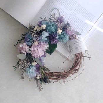 あじさいやベリーなどのスモーキーカラーでまとめたリースは、小花をちりばめてボリュームたっぷりなのに落ち着いた雰囲気。