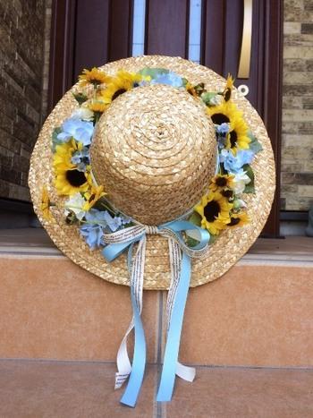 丸い土台の代わりに、麦わら帽子でリング状にしたリース。使わなくなった麦わら帽子をリメイクして、可愛く飾ってくださいね。