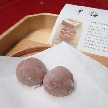 「葵祭」の名物を140年ぶりに復刻させたという「申餅(さるもち)」は、ほんのり赤い「はねず色」。その昔、神前に供えられていたのだそう。  中には小豆がぎっしり。ほうじ茶か黒豆茶とセットにできます。