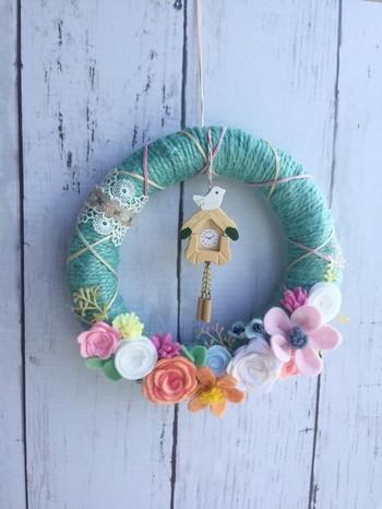 ジュート毛糸をグルグル巻いて、フエルトの小花で飾り付け。真ん中の小さな鳩時計がアクセントのリースは、プレゼントにしたら喜ばれそうです。