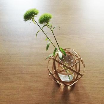 丸く編まれた竹の中にガラスの器が入った「くす玉花入れ」。ナチュラルな竹が爽やかなグリーンと優しくマッチしています。