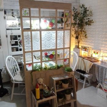 白くペイントしたドアを作ってリビングの間仕切りに。ステンドグラス風シートや植物を飾って可愛いカフェのような雰囲気に。