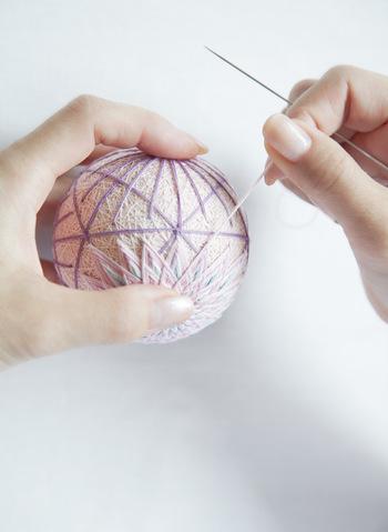 テキストを見ながら、木綿糸をまりにかがっていきます。模様が少しづつ、できあがっていくのが楽しい。
