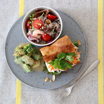 """人気のベトナムサンドイッチ""""バインミー""""。にんじん、大根、パクチーやお肉など、具材をたっぷりと挟んで1日の活力にしましょう。サラダなどは小皿に入れることで、プレート全体のバランスをとることができます。"""
