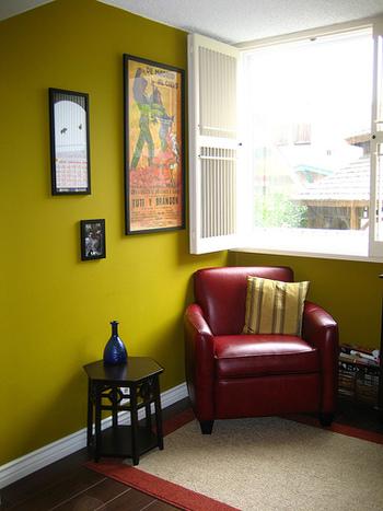 マスタードイエローが個性的な雰囲気の壁。シックな赤のソファとのコントラストも楽しいですね。