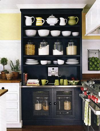 パステルイエローをポイントで取り入れたキッチンは、黒の食器棚でスタイリッシュな印象に。目線を上に行かせることで、天井をより高く見せています。見せる収納も素敵ですね。