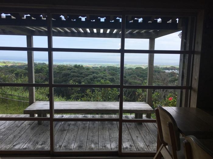 店内の大きな窓からは、緑あふれる絶景と、遠くにコバルトブルーの海が広がります。天気の良い日は、テラス席でのんびり景色を眺めたいですね。