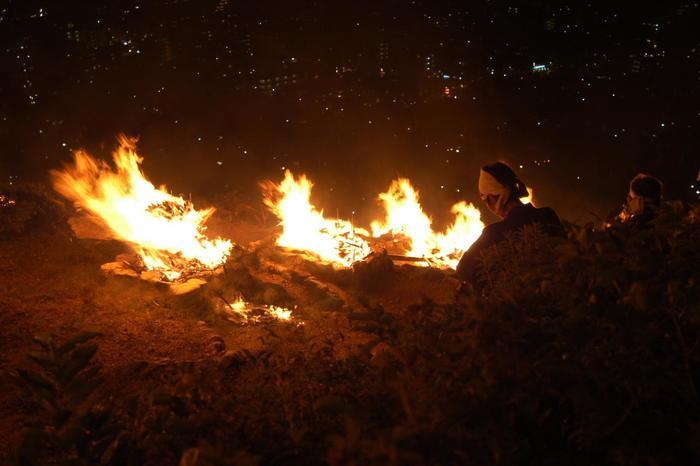 """全国に知られる「五山送り火」は、祇園祭と並ぶ、京都の夏を彩る風物詩。送り火が終わると、猛暑の夏とお別れです。  """"送り火""""は、招き入れた先祖の霊や精霊を冥府へと送り返す宗教行事です。各戸の前や墓前等で個々に行うものから、海や山で大規模に集団で行うものまで様々です。場所や灯し方、""""送り火""""の意味合いや由来も、地域それぞれで違いがあります。 【画像は、""""左大文字""""の送り火当日の様子。】"""