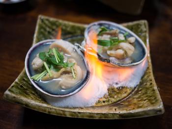 愛知県で獲れた大アサリを焼き上げるメニューも大人気。目の前で炎を上げる焼き大アサリは、地酒と一緒に味わいたい逸品。
