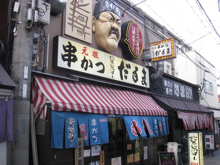 串カツの発祥とされる新世界の「だるま」は、観光客にも大人気。活気ある店内で仲間とワイワイ串カツを楽しんで。