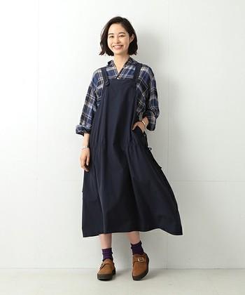 チェックのシャツに合わせたエプロンワンピはどこかカントリー調。 シャツの素材は、写真のように柔らかいものを選ぶと、ボーイッシュになりすぎません。