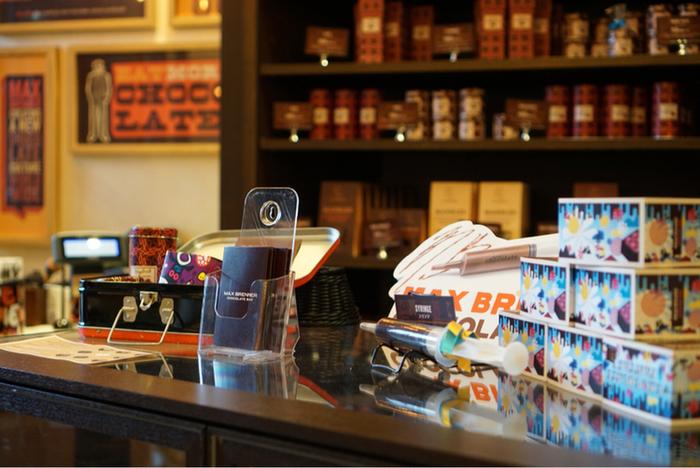 ダークブラウンの内装が大人っぽい雰囲気の店内。壁一面にギフト用のチョコレートやマグカップなどがレイアウトされていて、順番を待っている間もわくわくします。