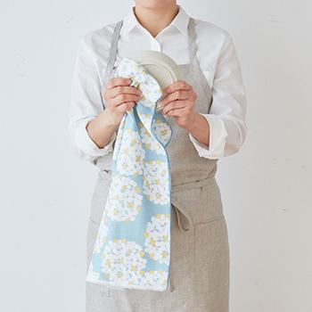 """手ぬぐいの""""ぬぐい""""は拭う(ぬぐう)の意味。本来は水に濡れたものをぬぐうものなんですね。  だからお布巾として、台所で洗った食器を拭う。それは定番の使い方でもあります。華やかで可愛らしい手ぬぐいがある風景は、キッチンを明るい雰囲気にもしてくれるはずです。"""