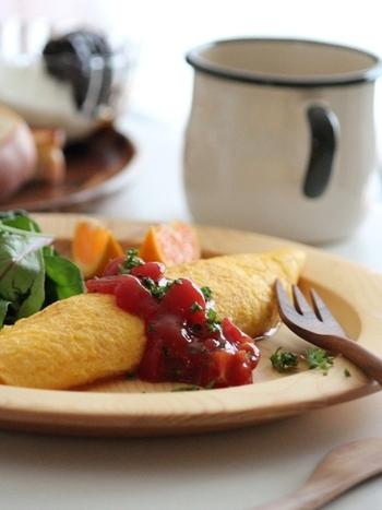 """オムレツを美味しく作るコツは、フライパンに卵を入れたら菜箸でよく混ぜて余熱で火を通すこと。余熱にすることで、とろっとした半熟に仕上がります。フライパンを斜めにして、柄をトントンと叩いて形成していきます。上手くできない方はヘラなどを使って巻いてもOK◎""""手早く""""仕上げるのもポイントです。"""