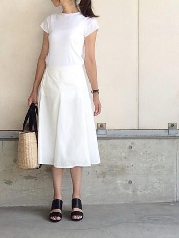 白のTシャツとスカートのホワイトコーデ。素材感が近いシンプルな組み合わせなので、広めの甲の黒サンダルを合わせると全体が引き締まりますね。