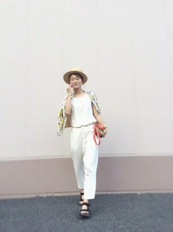 ホワイトコーデは、どんな色柄のアウターにも合わせやすいのが魅力。イエロー系のトロピカル柄のカーディガンを羽織った夏らしいコーデです。