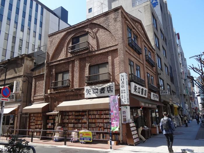 靖国通りの角地に佇む大正7年創業の老舗「矢口書店」は、風情ある雰囲気も魅力です。石造りの建物に見えますが木造の3階建て、昭和3年に建てられました。 映画・演劇・演芸・戯曲・シナリオ専門店で、難しそうな本を扱っているように見えますが、アイドル本やマンガなどもあり気軽に立ち寄れます。