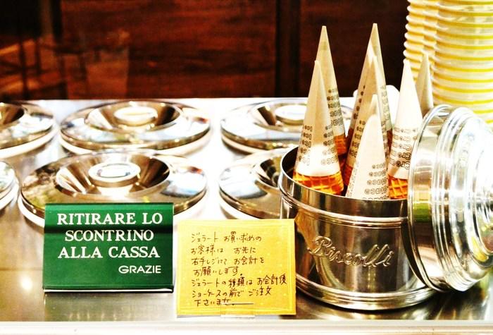 本場イタリア仕込みのジェラート屋「GELATERIA ACQUOLINA」。 ショーケースに並ぶジェラートは蓋がされていて見えないのですが、デリケートなジェラートをできるだけ空気に触れさせないためのこだわりなんだとか。 名前を見てどんな味か気になった場合は、スプーンで味見もさせてもらえます。