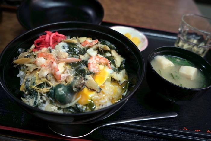 """志賀島は新鮮な海鮮を食べられるのも魅力。こちらは志賀島の大人気店「中西食堂」の『曙丼』。サザエ・エビ・わかめを卵でとじた大人気メニューです。芸能人も訪れる名店で、店内は""""昔ながらの食堂""""といった懐かしい雰囲気が漂います。"""