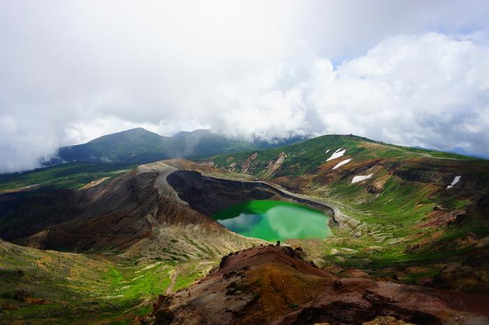 山がぽっかり口を開け、そこにたたえられている深緑色の水。自然の創り出す美しさとスケール感が楽しめる場所が宮城側にある蔵王連峰のもう1つの人気スポット「御釜」です。ここは4月下旬から11月初旬までしか見られない、期間限定のスポットなんです。