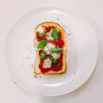 いつものトーストにトマトソースとモッツァレラ、バジルをのせてピザのように作れるトーストです。  トマトの酸味とチーズの風味がよくマッチした味わいが楽しめますね。  トマトソースはケチャップでも代用できますが、トマトソースを常備しておくと、このようなごちそうトーストがいつでも楽しめそうです。