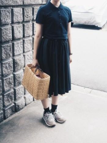 シンプルな黒いポロシャツ×スカートのコーディネート。アジアンな雰囲気のカゴバッグに合わせると、エスニックアクセサリーが自然に馴染みますね。