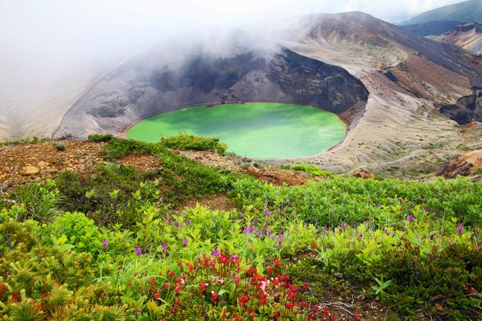 御釜は通常深い緑色の水をたたえていますが、太陽の当たり方によってコバルトブルーやエメラルドのような色に変化します。その原因は水質と言われています。御釜の水は硫黄分が強くpH3.5という強酸性で生き物は住むことができませんが藻類の中には、適応して生きているものもいます。