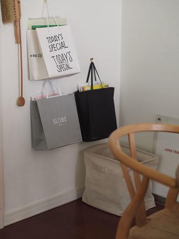 シンプルなショップバッグやエコバッグなど、サイズがほぼ同じものを選んで壁に掛ければ立派な壁掛け収納に。毎日出し入れするようなものや、お子様のプリント類などもオシャレに収納できます。