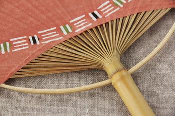竹の丸みを生かした「丸柄」は、「房州うちわ」の特徴のひとつ。竹を細かく裂いた骨が窓から放射線状に見え、美しい佇まいです。