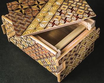 箱根寄木細工は木材のそれぞれが持つ異なった材色や木目を生かしながら寄せ合わせ精緻な幾何学文様を作り出し、そのまま加工し製品にしたり、特殊な大鉋(おおかんな)で薄く削り、小箱などに貼布、装飾に利用したりする伝統的な木工芸品です。  製品としては箱を開ける際のからくりが施してある秘密箱が有名ですが そのほかにもコースターやお皿、箸置き、ボタンなども。  箱根ではこの寄木細工を体験できる施設がたくさんあります。