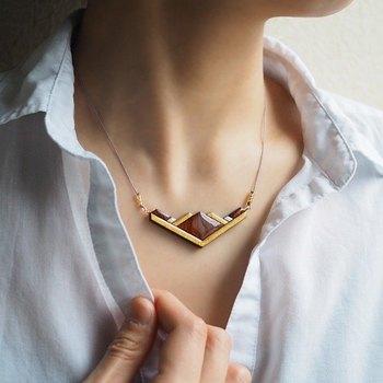 珍しいカリンの木のネックレス。 1つ1つ表情が違う木目素材には、ぜひ綿やリネンの自然派シャツを合わせたい。
