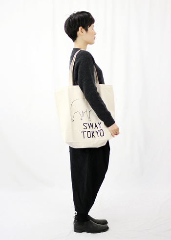 ホワイトカラーのシンプルなロゴトートは、ブラックコーデに合わせるとバッグが引き立ちます。