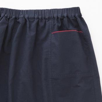 ポケットと裾には赤いラインがポイントに。このラインも生地の耳の部分を生かしてデザインされています。