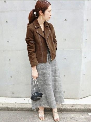 グレンチェックのフレアスカートは上品な雰囲気。ハードなイメージのライダースジャケットも女性らしくコーディネートすることができます。