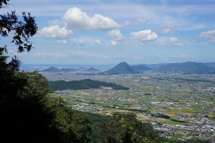 """奥社である「厳魂神社(いづたまじんじゃ)」からの眺め。琴平の町はもちろん、晴れた日は瀬戸内海まで一望できます。  一生懸命のぼった人だけが、この絶景を味わえますよ。参拝のあとは、香川名物の「讃岐うどん」巡りもいいですね。暑い夏なら、""""おいり""""入りのソフトクリームもおすすめです。"""