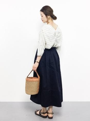 襟足が美しく見える抜襟のブラウスをスカートにin。カゴバックとサンダルが夏らしさを演出してくれています。ヘアもルーズにまとめて後姿を印象的に。