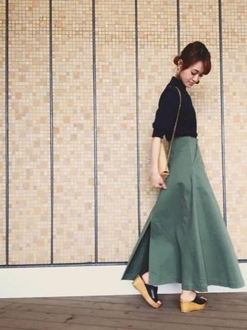 黒のトップスにカーキのロングフレアースカートを合わせています。シックな色味とタイトなシルエットが大人っぽい雰囲気です。
