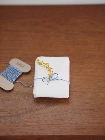 とても儚げなラッピングアイデアです。木の実や小花は、細いカラー紐でくるりと巻くとキュート。