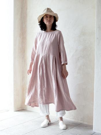 淡いピンクのゆったりシルエットのワンピースを、白いアイテムと合わせた、甘く爽やかな着こなし。